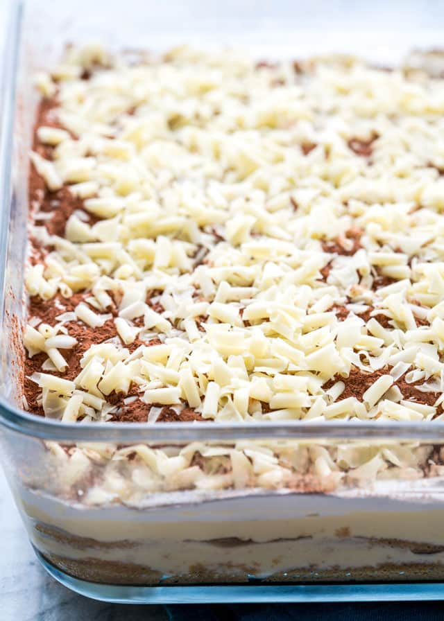 a pan of tiramisu topped with white chocolate shavings