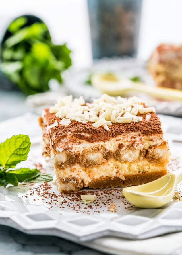 a slice of tiramisu on a plate with white chocolate shavings and mint