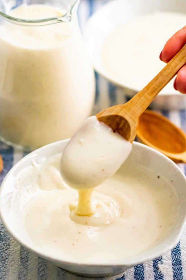 bechamel sauce in a white bowl with a hand taking a spoonful of it