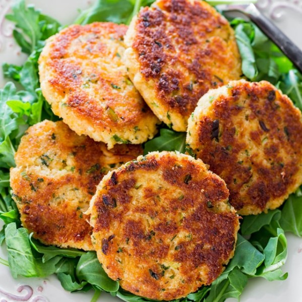crab cakes sitting on top of a plate full of greens