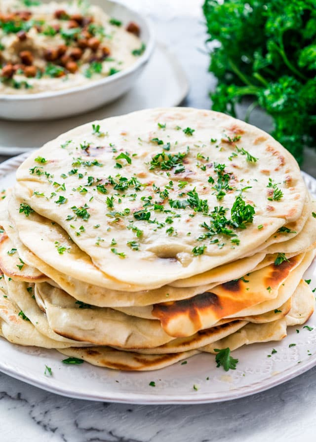 a plate full of naan bread with hummus in the back