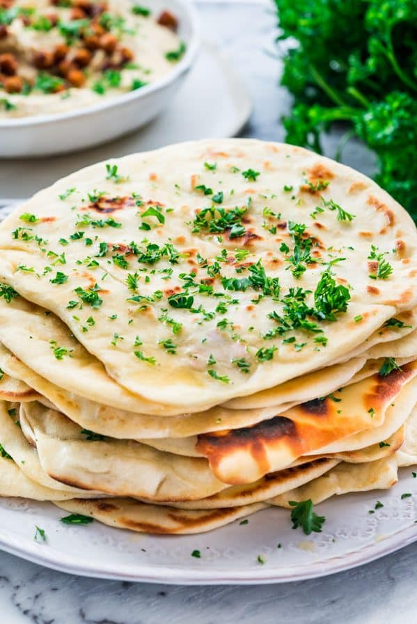 side view shot of a stack of fresh naan bread on a plate