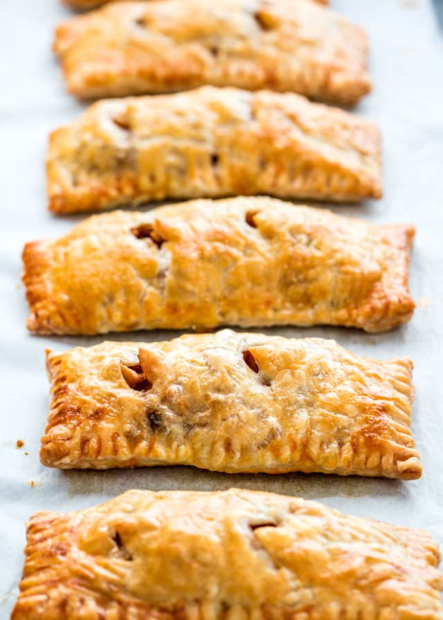 5 apple turnovers lined up on a baking sheet