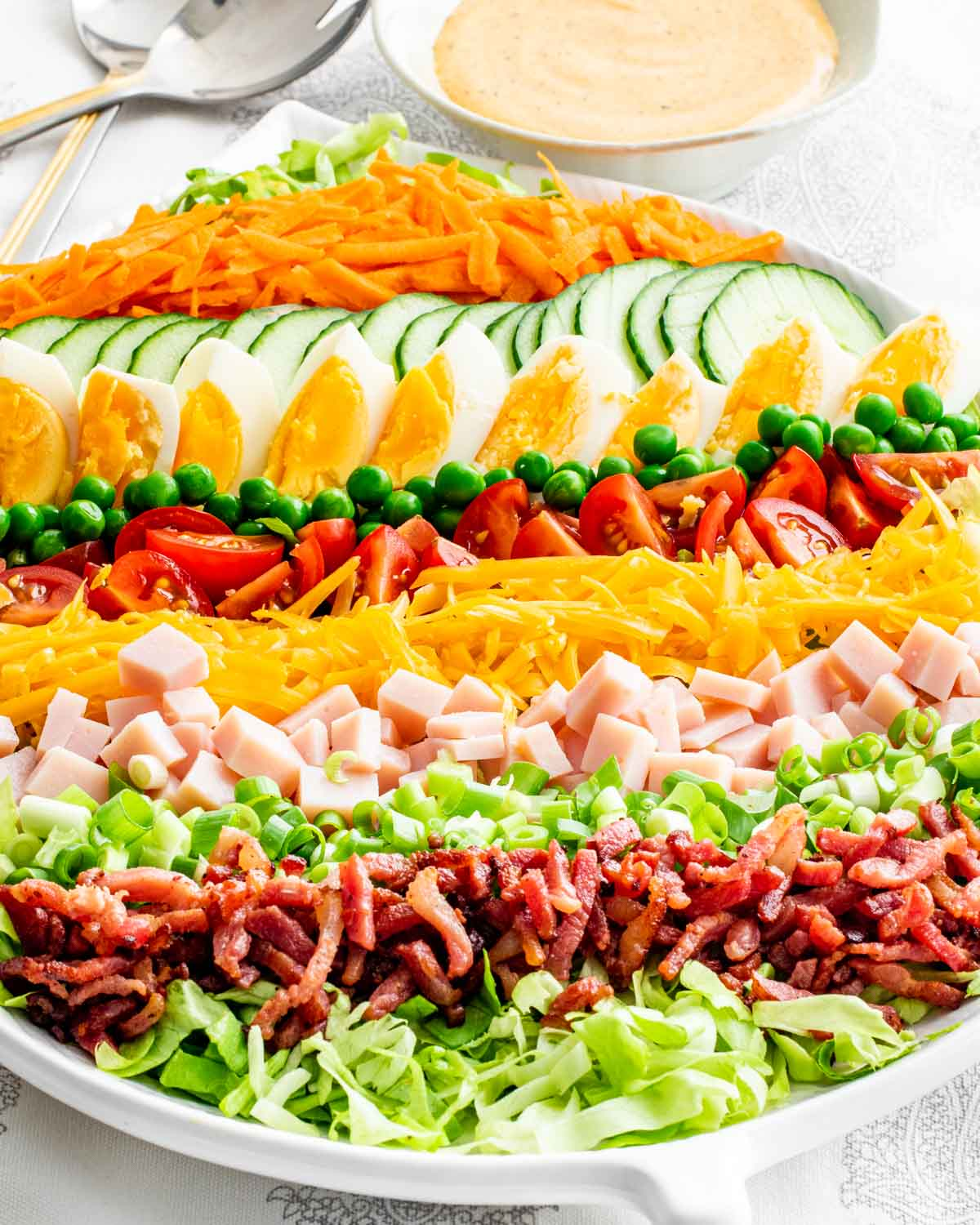sideview shot of a layered chef salad in a white serving bowl