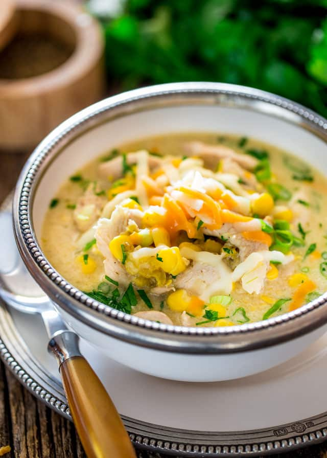 a bowl of Chicken and Corn Chowder topped with green onions and cheese