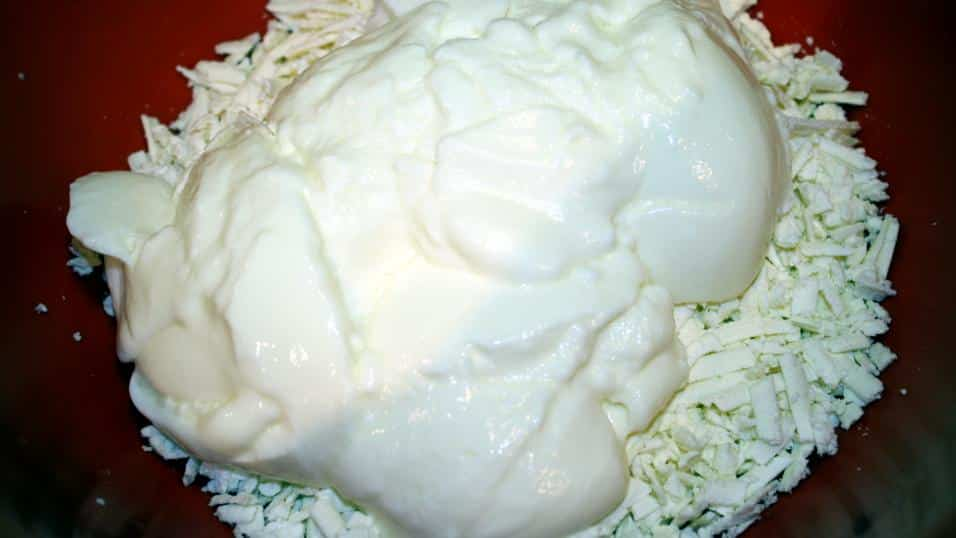 Plain yogurt is added to the bowl of shredded feta