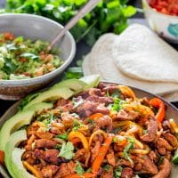 a plate full of the pork fajita filling garnished with sliced avocado