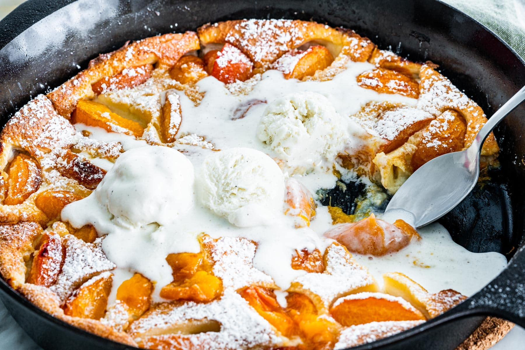 side view shot of apricot clafoutis in a black skillet with a couple scoops of ice cream on it