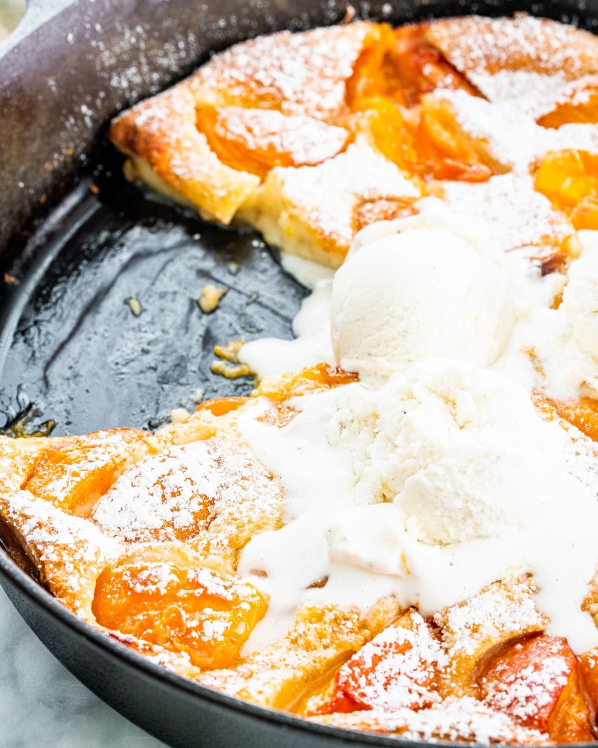 closeup shot of apricot clafoutis in a black skillet with a couple scoops of ice cream on it