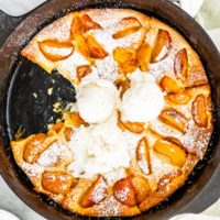 overhead shot of apricot clafoutis in a black skillet with a couple scoops of ice cream on it