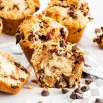 chocolate chip muffins, one cut in half with butter spread in the center