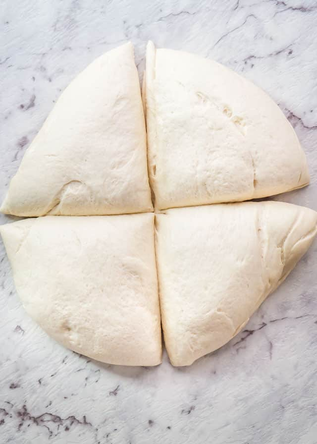 freshly made pizza dough cut in quarters