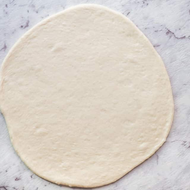 rolled out pizza dough ready for toppings