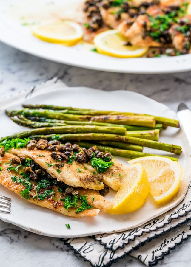 Sole Meuniere on a plate with asparagus and lemon wedges