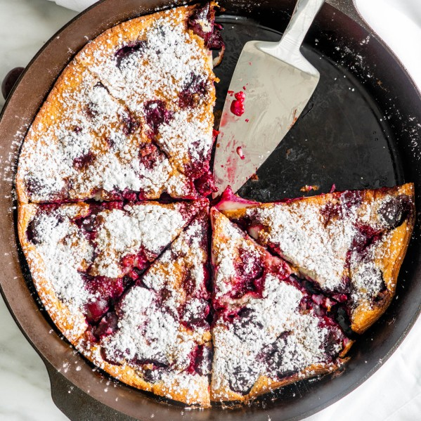 overhead shot of cherry clafoutis in a pan with two slices missing and a pie lifter in the empty space