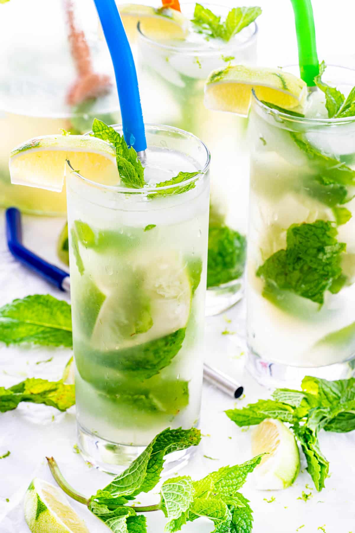 a couple glass with mojitos and straws in them