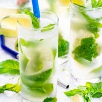 mojito cocktails in tall glasses with mint, limes and straws