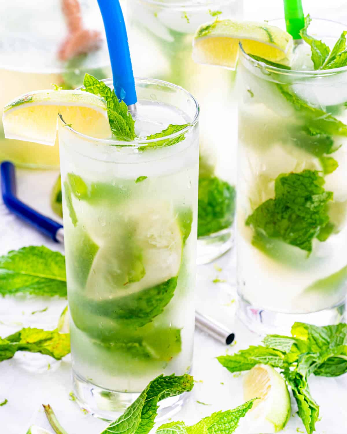 a couple glasses filled with mojitos and garnished with limes and mint