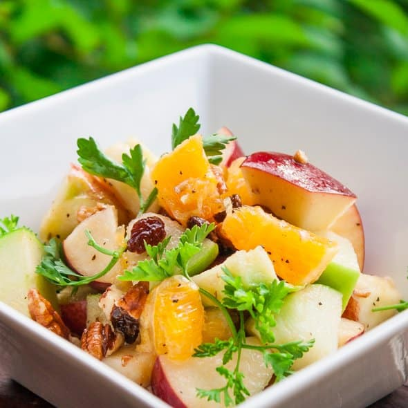 orange and apple salad garnished with parsley in a bowl