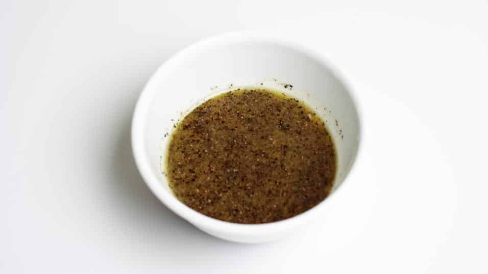 A bowl of dressing made with mustard, salt, pepper, red wine vinegar, lemon juice, orange juice, sugar and olive oil