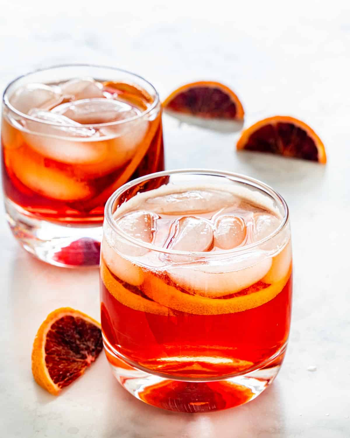 americano cocktail in two glasses garnished with blood orange