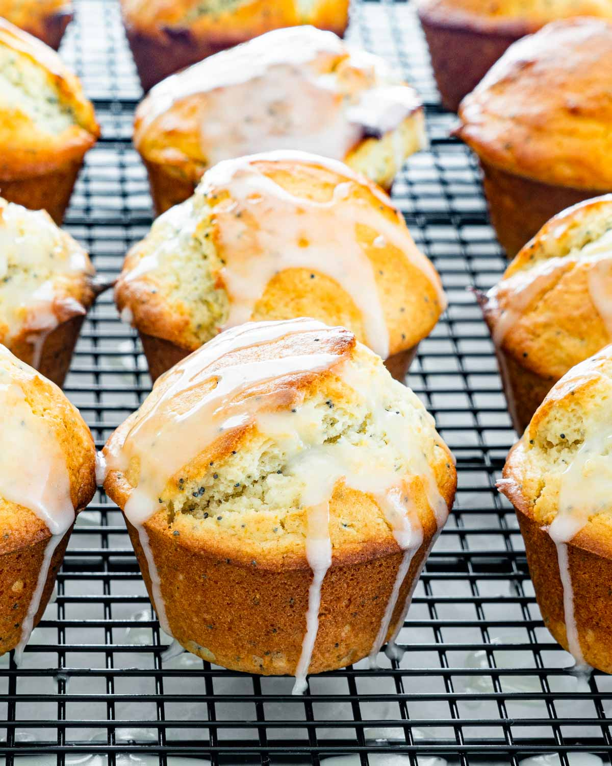 lemon poppy seed muffins with lemon glaze on a cooling rack