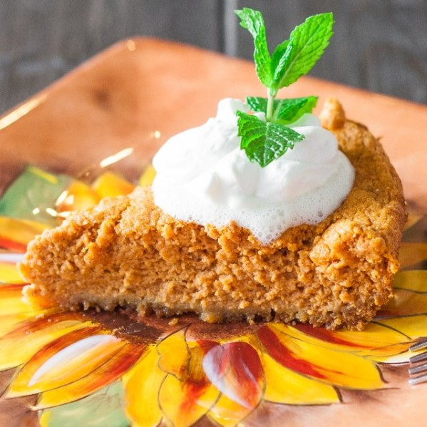 a slice of pumpkin pie with graham cracker crust topped with a dollop of whipped cream