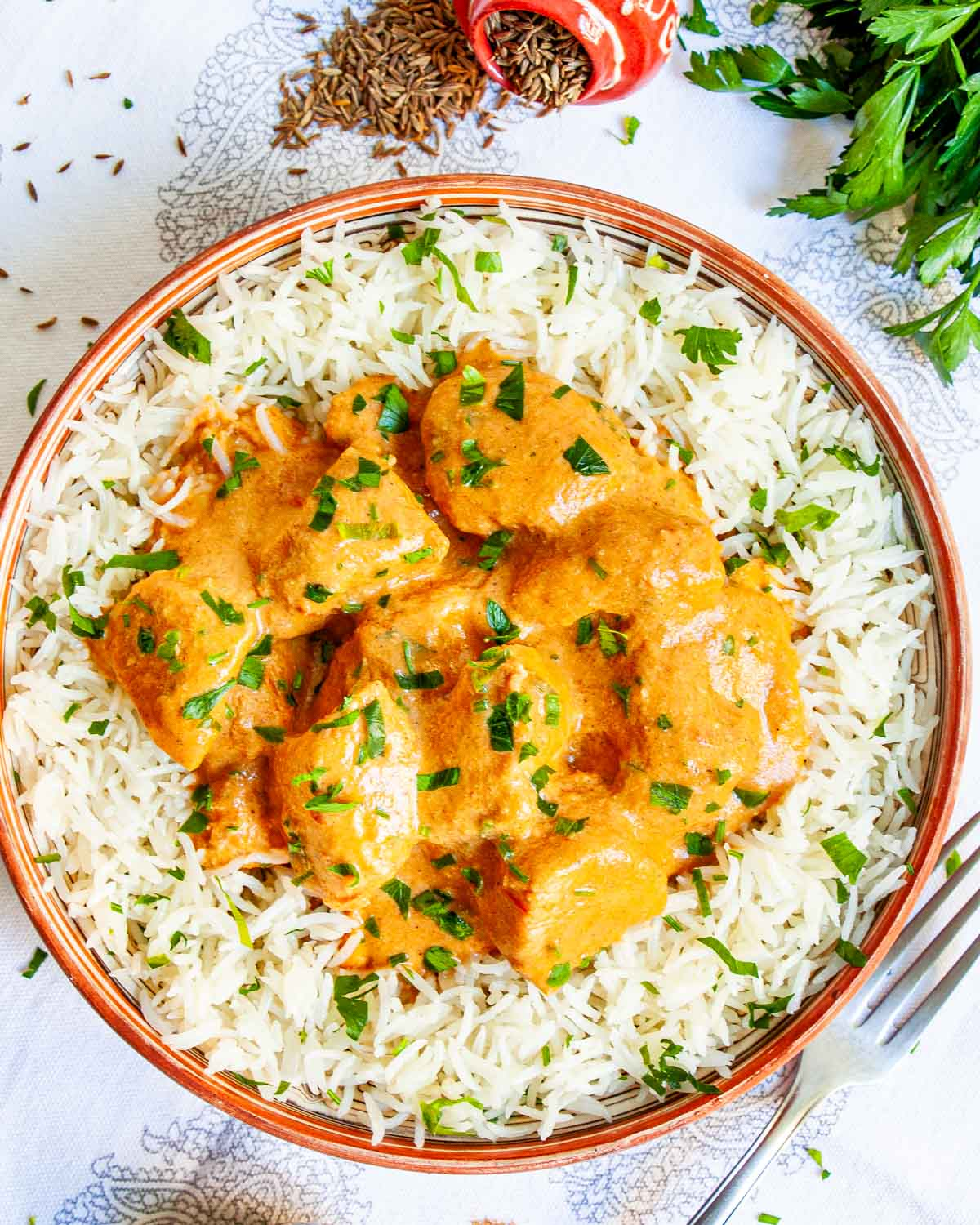 overhead shot of butter chicken on a plate over white rice garnished with parsley