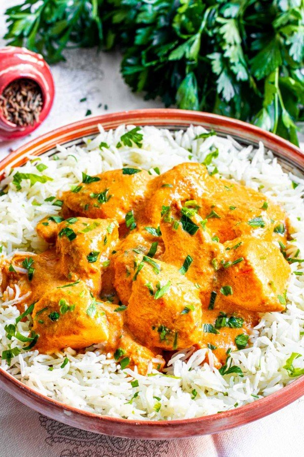 sideview shot of butter chicken on a plate over white rice garnished with parsley