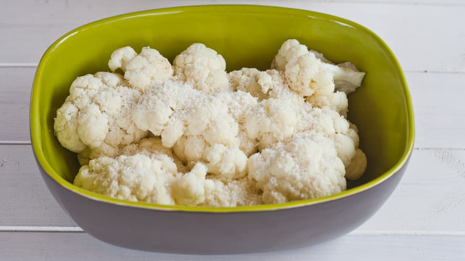 Bowl of cauliflower sprinkled with parmesan cheese