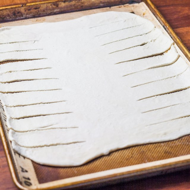 Puff pastry on a baking sheet with slices down the sides