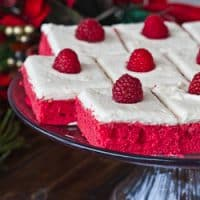 red velvet cake slices topped with fresh raspberries