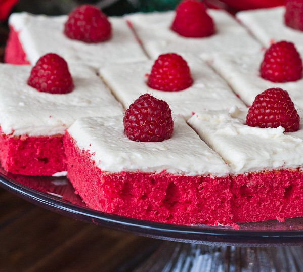 red velvet sheet cake slices topped with fresh raspberries