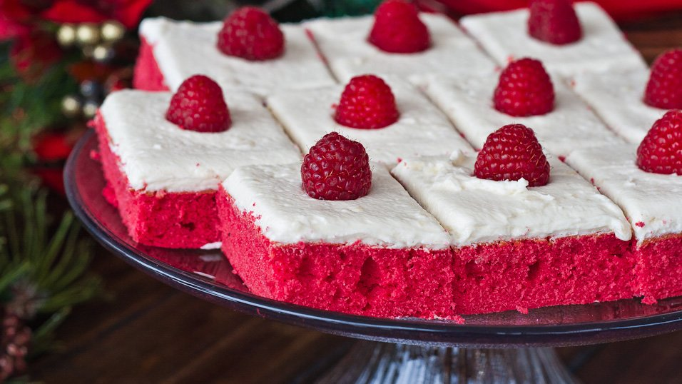 Red Velvet Sheet Cake cut into squares topped with raspberries