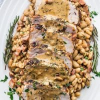 overhead shot of sliced rosemary garlic pork roast covered in gravy on top of white beans on a serving plate garnished with rosemary sprigs