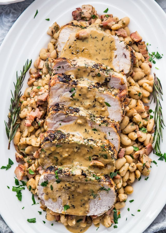Overhead of sliced Rosemary Garlic Pork Roast on a bed of beans