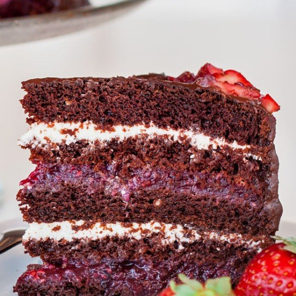 a slice of chocolate cake with mixed berry and cream cheese filling on a plate