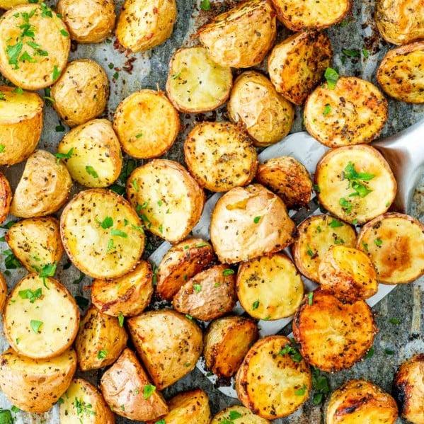 overhead shot of roasted baby potatoes on a baking sheet.