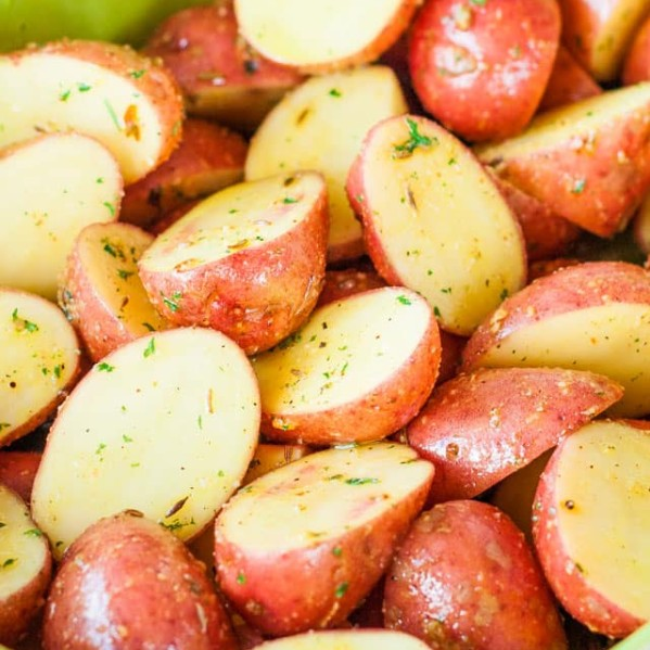 a bowl full of uncooked potatoes with spices