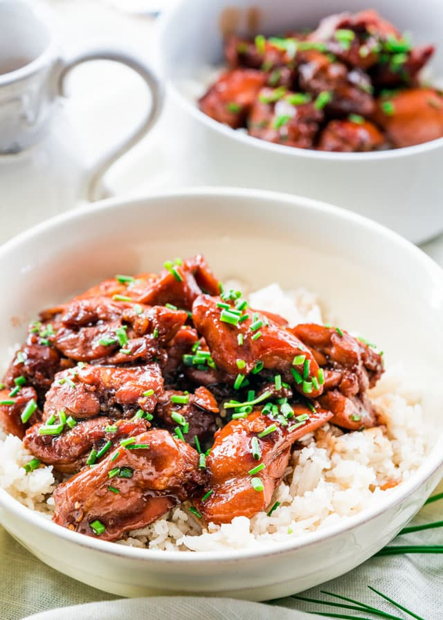a bowl of saucy bourbon chicken over rice