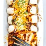 overhead shot of enchiladas in a casserole dish freshly baked with 2 enchiladas missing and a spatula in their place