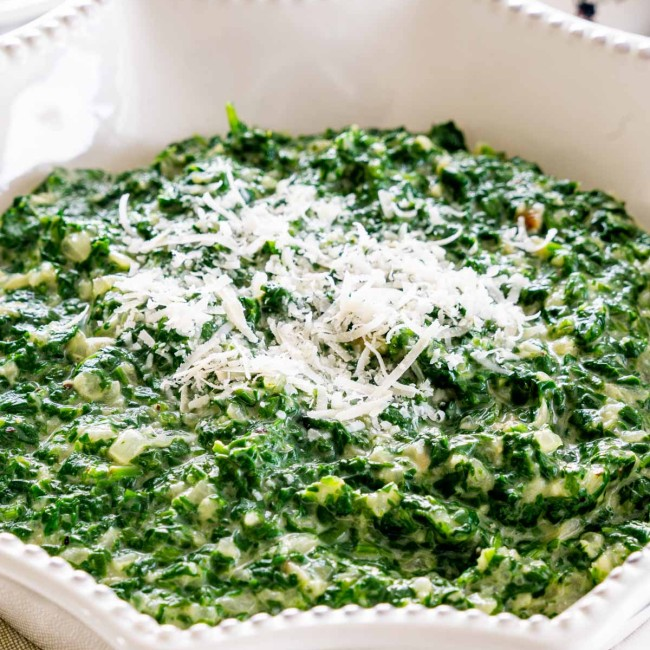 creamed spinach in a white bowl garnished with parmesan cheese.
