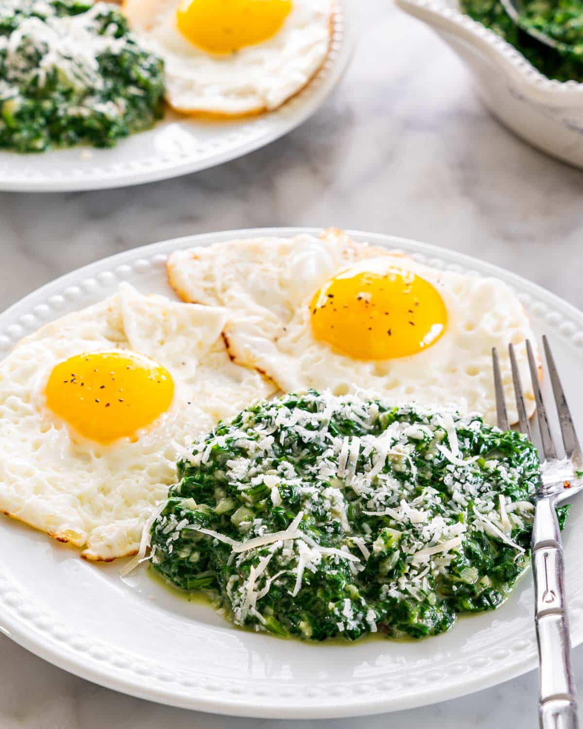 creamed spinach with 2 sunny side eggs on a plate.