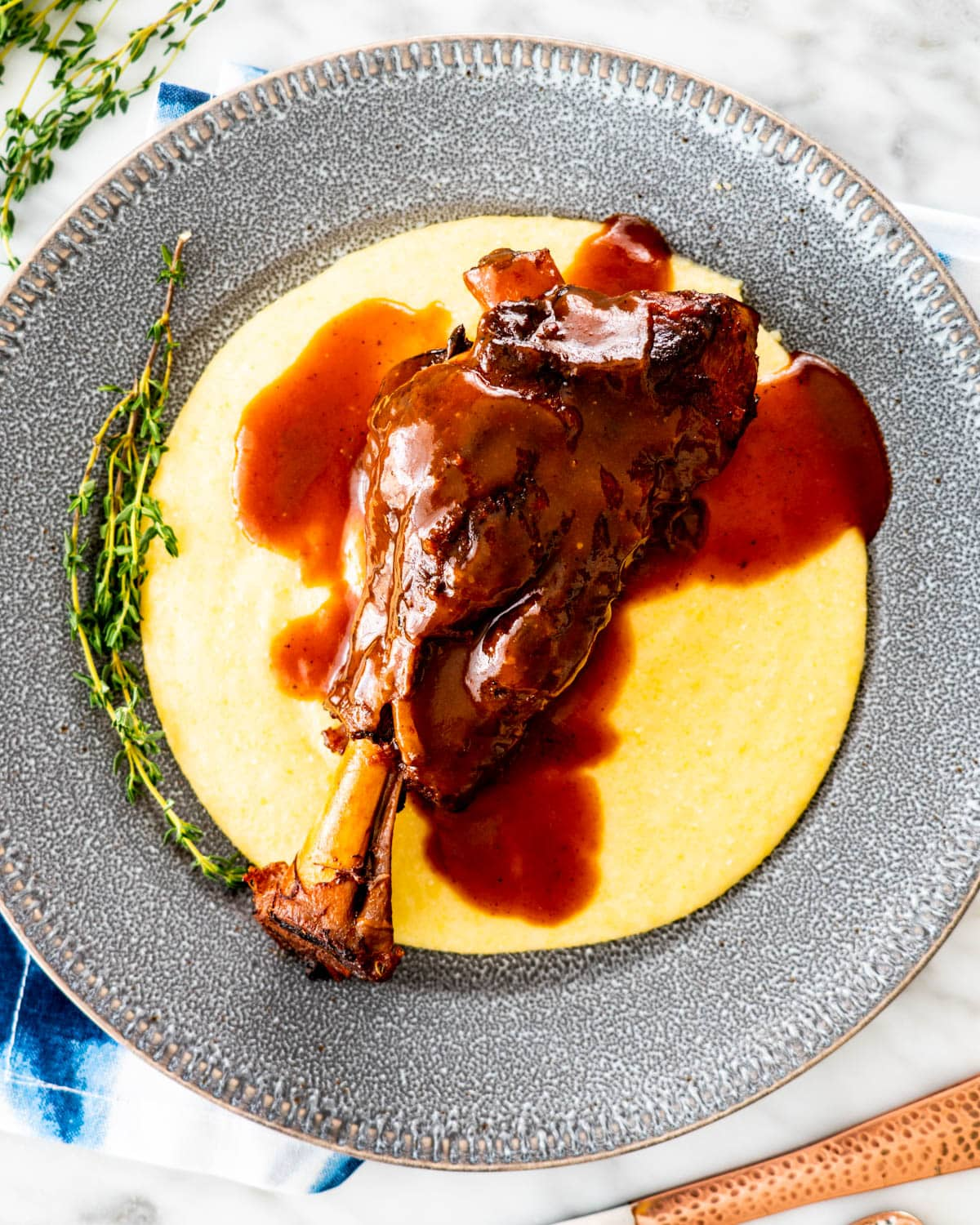 overhead shot of braised lamb shanks over creamy polenta