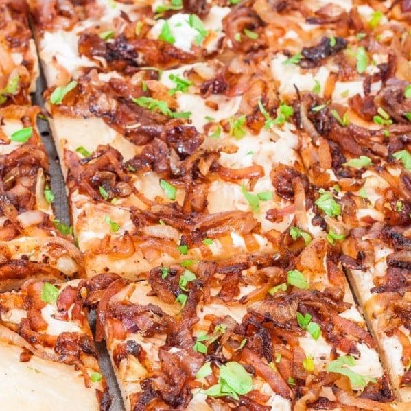 close up shot of a caramelized onion flatbread sliced into squares