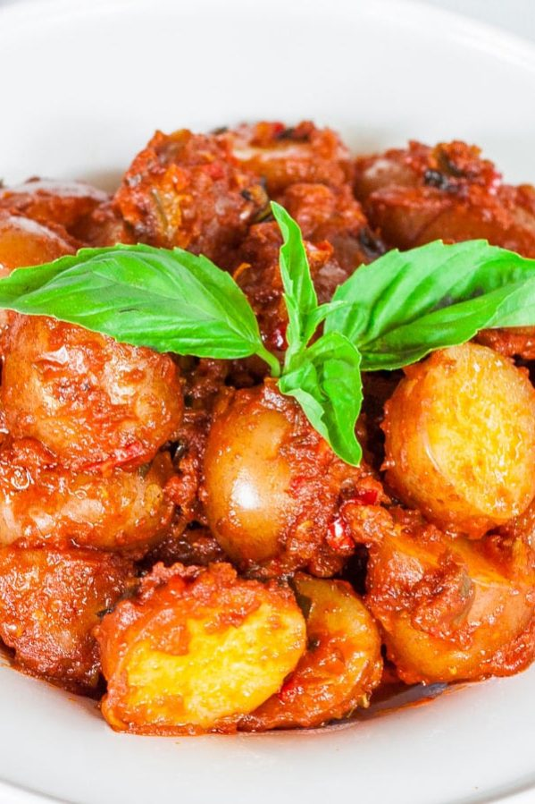a bowl of potatoes in hot red sauce topped with a sprig of basil