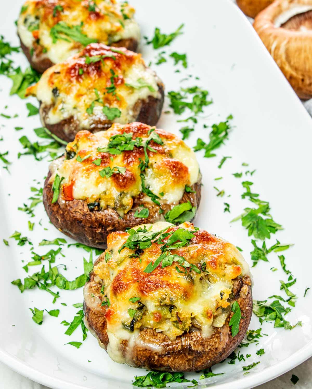 stuffed portobello mushrooms on a serving platter garnished with parsley.