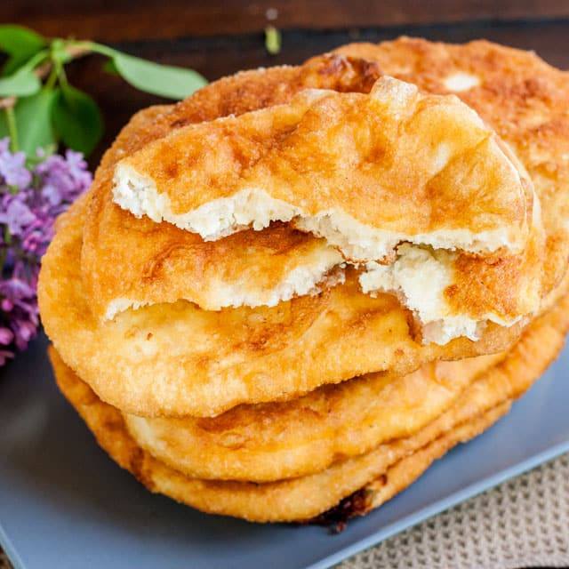 """overhead shot of Fried Dough Filled with Feta Cheese a.k.a. """"Langosi cu Branza"""" stacked up on a blue palte"""