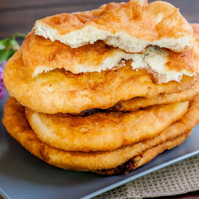 """Fried Dough Filled with Feta Cheese a.k.a. """"Langosi cu Branza"""" on a blue plate with one ripped in half"""