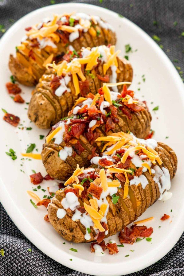 hasselback potatoes on a serving platter garnished with sour cream, bacon and cheese.